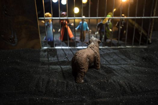 People and animals on opposite sides of the fence concept. Creative decoration with toy figures. Burning colorful background. Selective focus.