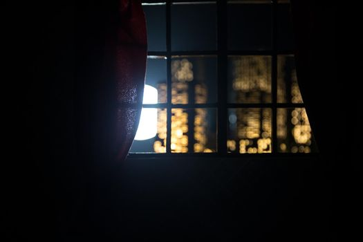 look through a window and city night view. Realistic dollhouse window and city miniature in selective focus.