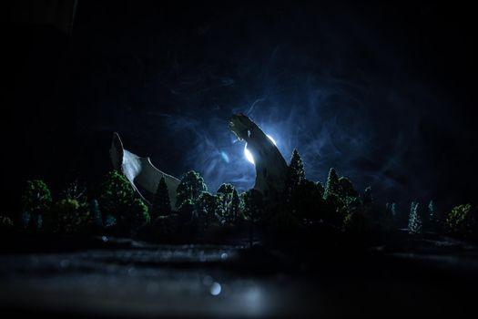 Abstract surreal concept. Giant animal bone in dark forest under moonlight. Night with fog and light on background. Selective focus