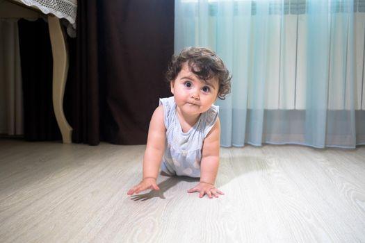 Baby Girl In Summer Dress Sit on wooden floor inside room. Baby girl sitting near window