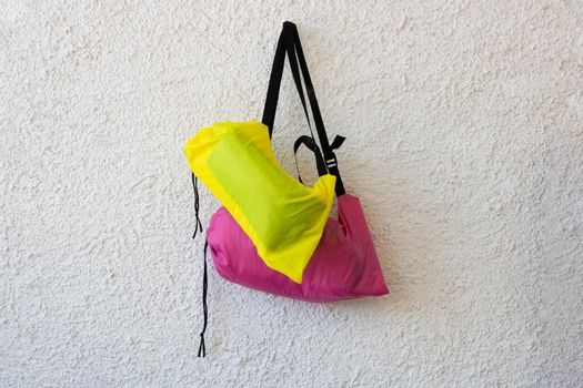 Pink and yellow sports bags with a black belt on a white rough background.