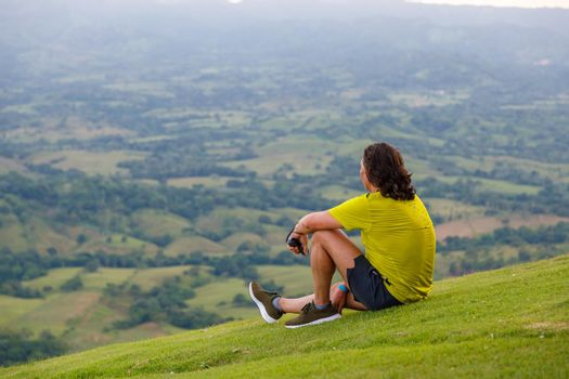 In summer, a man with long hair sits on the green slope of the mountain, looking into the distance at the valley. Dominican Republic, sunset in the mountains