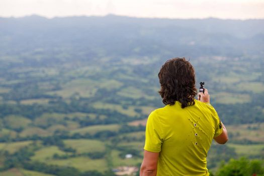 A long-haired man filming a video with a small video camera, a picturesque valley. Dominican Republic on the mountain.