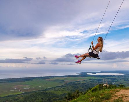 A young girl, blonde, swinging on a swing on a mountain slope in summer. Swing high in the mountains above the valley. Dominican Republic. Setting sun