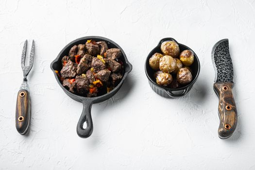 Beef stew goulash - rustic style, in cast iron frying pan, on white stone surface, with copy space for text