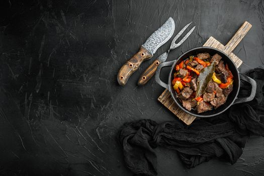Irish stew made with beef, potatoes, carrots and herbs, in cast iron frying pan, on black stone background, top view flat lay, with copy space for text