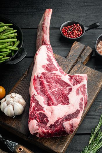 Raw fresh tomahawk black angus prime beef chop steak, with grill ingredients, on black wooden table background