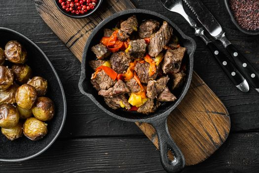 Mongolian beef, pieces of beef stewed in soy sauce, in cast iron frying pan, on black wooden background, top view flat lay