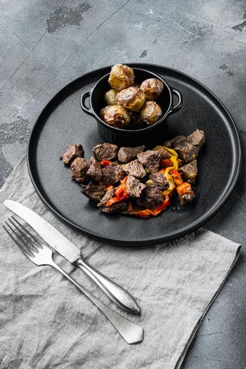 Meat stew with sweet bell pepper and bay leaf, on gray stone background