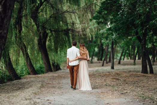 a guy and a girl are walking along the banks of a wild river overgrow