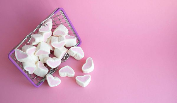 Valentine's Day, top view. Marshmallows pink hearts spilled out of a toy basket on a pink background, copying the space, the concept of love. The concept of buying love