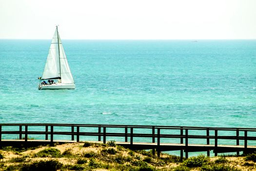 Sailboat sailing along the coast on a sunny day in Spain