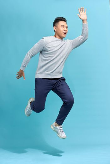 Full-length photo of funny man running or jumping in air isolated over blue background