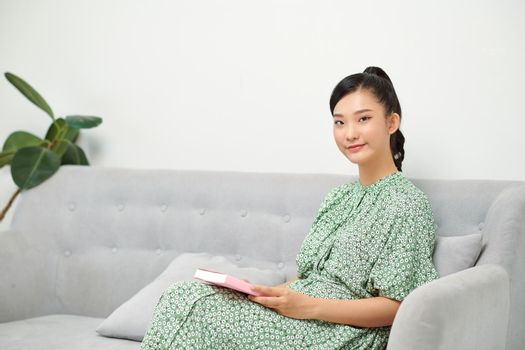 Young woman reading humorous novel while sitting on sofa