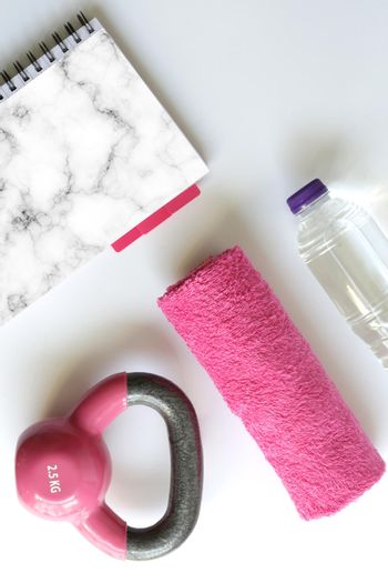 sport feminine accessories, flat lay, Pink dumbbell pink notepad for mock up, copy space. Gym accessory and equipment in pink feminine color. Fitness and healthy lifestyle, mock up