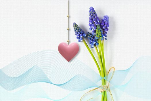 Festive spring blue flower composition on white background with ribbon and hanging 3d pink heart