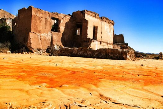 Colorful orange sediments deposited in a dry lake of an old abandoned mine in Mazarron, Spain. Old abandoned house in the background.
