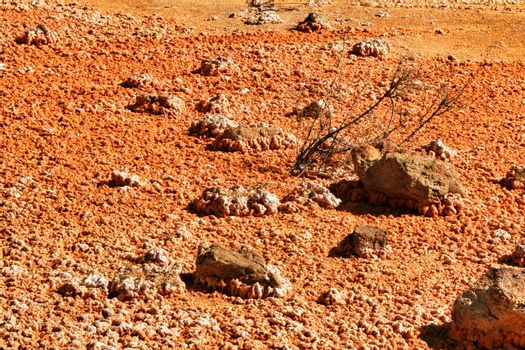 Colorful orange sediments deposited in a dry lake of an old abandoned mine in Mazarron, Spain