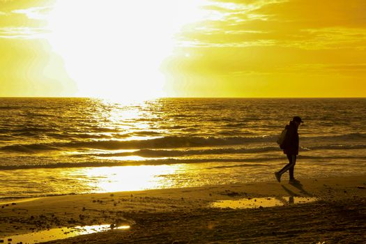Beautiful Sunrise on the beach with pink and orange colors in Arenales del Sol, Alicante,southern Spain. Woman looking at the horizon.