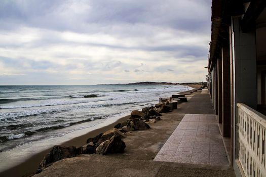 Rough sea under Cloudy sky in winter in La Marina beach in Alicante, Spain.