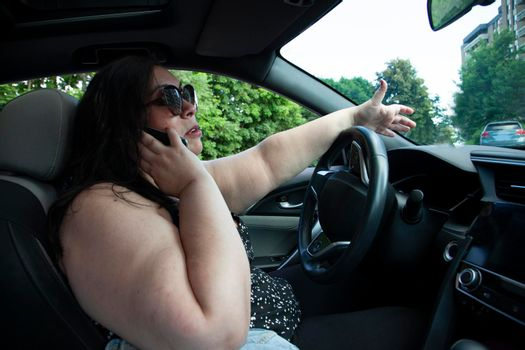 side view inside car with woman on cell phone