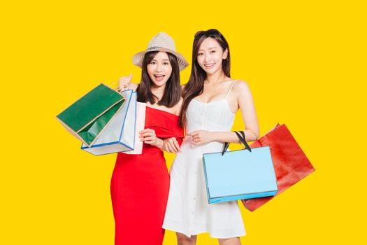 happy young women dressed in summer clothes holding shopping bags