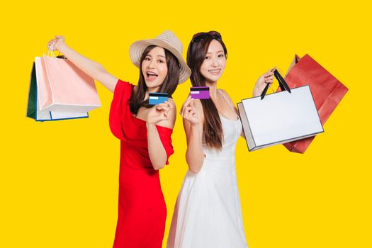happy young women dressed in summer clothes holding shopping bags and credit cards