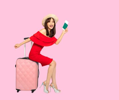 Happy young Woman traveler with suitcase on pink background