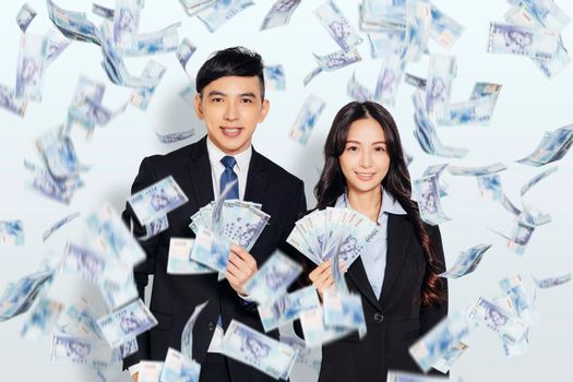 young business man and woman showing the money under the money rain