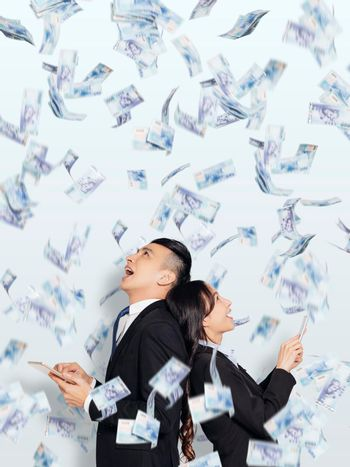 Excited young business man and woman holding smartphone and watching the money rain