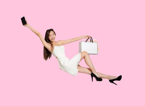 Happy young woman holding mobile phone and shopping bags while flying