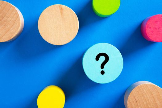 Question mark icon on blue wooden block on blue background.