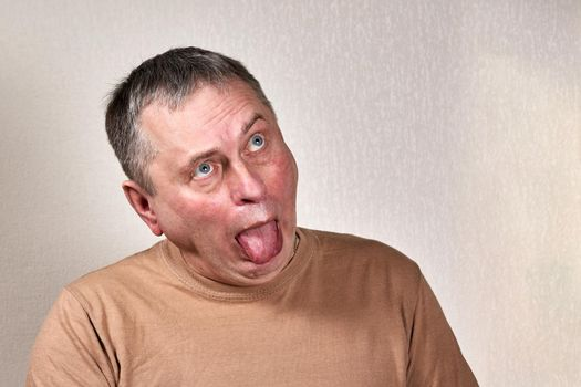 Freak man with bulging eyes stuck out his tongue in the studio
