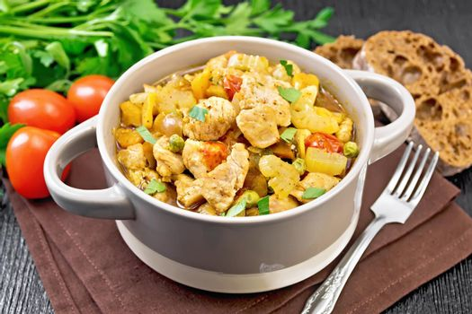 Chicken with vegetables and peas in saucepan on table