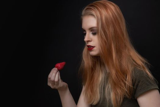 Beautiful long hair young woman is posing with strawberry.