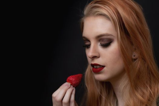 Beautiful long hair young woman is posing with strawberry closeup.