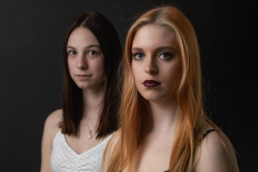 Pair of serious young women is posing on the black background.