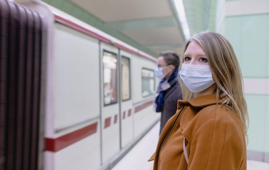 People in public transport wearing covid-19 face mask while train arrives