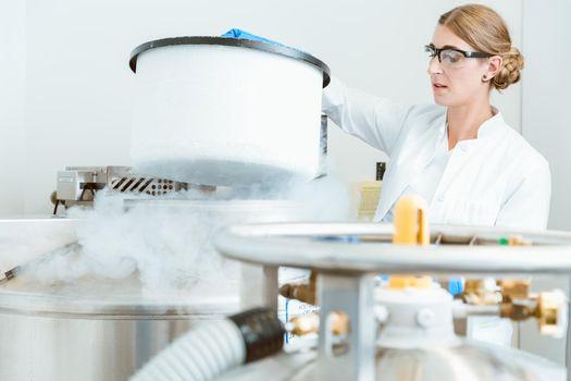 Scientist lifting machine lid of machinery