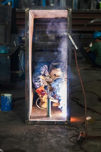 Blue-collar worker welding in the interior of a factory