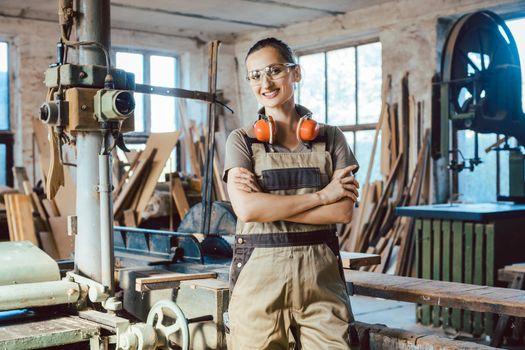 Beautiful woman carpenter in her woodwork workshop