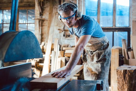 Carpenter working on wood with the circular saw