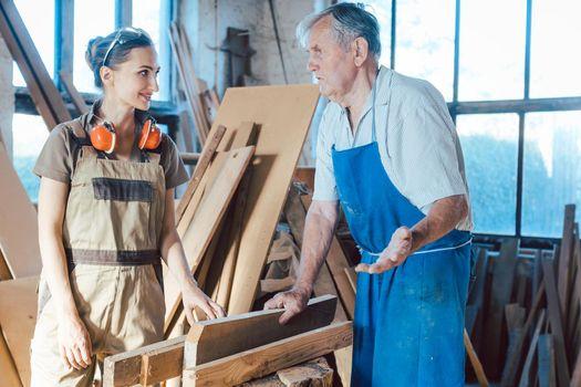 Senior carpenter sharing wisdom with younger aspiring colleague