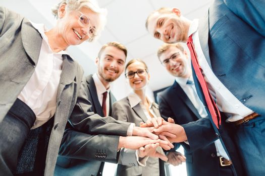 Business Team stacking hands looking at camera