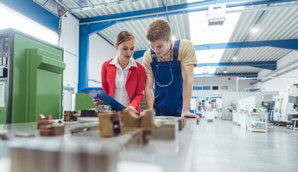 Manufacturing worker and manager during quality inspection