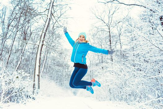 Cheerful woman in sports clothing enjoying the winter and snow
