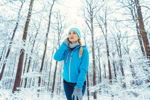 Woman wearing functional clothing in snow warming up for sports