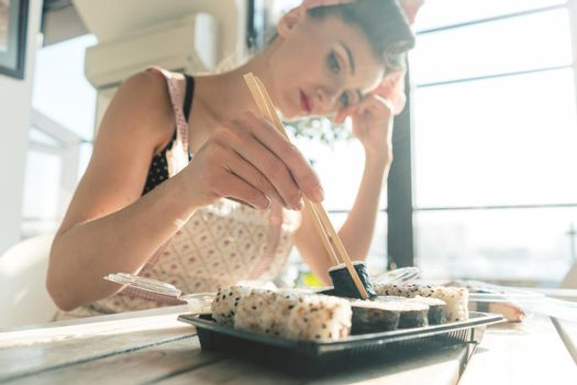 Homemaker woman resting from housework eating some sushi