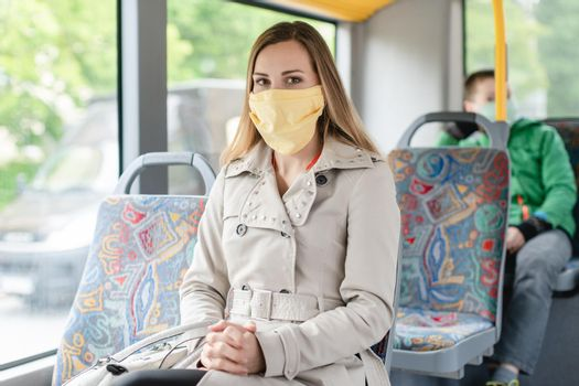 Woman using public transport during covid 19 crisis wearing face mask