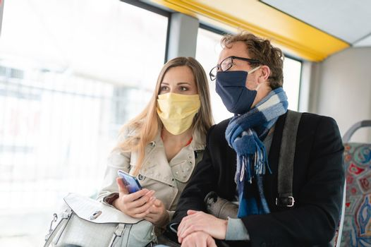 Couple in public transport bus wearing masks, man and woman